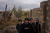 Baku, Azerbaijan .December 14, 2006..Just a few meters from the British Petroleum's massive multi-billion dollar off-shore platform being built on shore, is one of the poorest districts near Baku. Most of the residents are refugees from Nagorno-Karabakh region settled here during the war...Children make their way home after school in the shadows of the old rigs and the new BP construction sight.