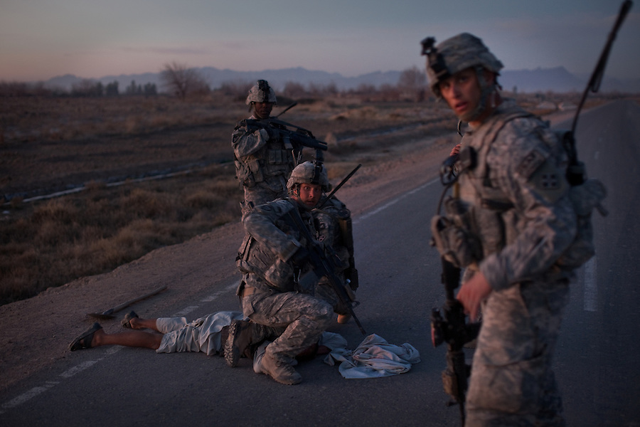 Soldiers with 3rd Platoon Charlie Co. 1st Battalion 12th Infantry Regiment, 4th Infantry Division briefly detain a young man seen running from the scene of a near-by brief exchange of fire between Charlie Company troopers and Taliban fighters on suspicion that he might be involved in planting an IED because of the shovel he was carrying. January 17, 2010. Zhari District, Kandahar, Afghanistan. The violently contested district sits astride the strategically Highway 1 ringroad between Kandahar and Lashkar Gah and is seen by some as the birthplace of the Taliban movement.