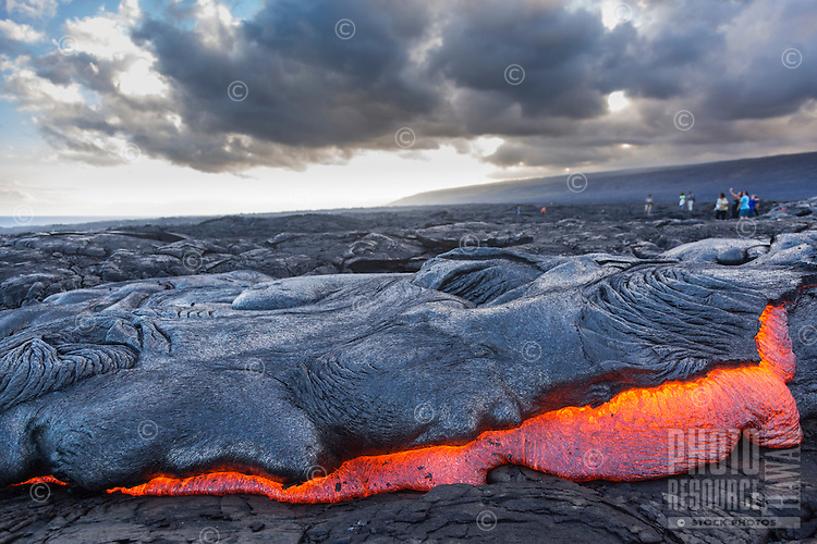Visitors marvel at the glowing molten lava flowing down the hill at (Hawai'i) Volcanoes National Park, Hawai'i Island.