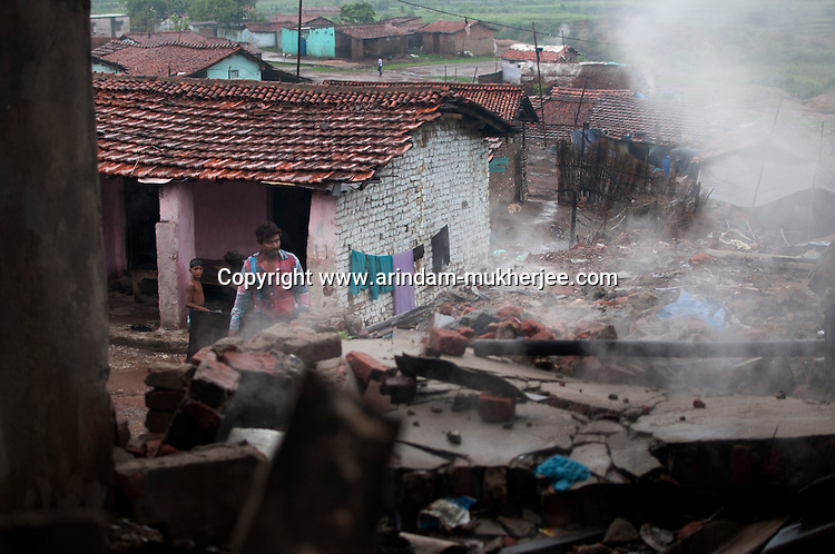 A man passes by the rubble of a recently destructed house at Indra chowk. Indra Chowk located at the border of Jharia town has also been affected by the mine fire. Even some 10 years ago the fire hadn't spread to the buildings at the area like now. A huge coal mine fire is engulfing the city of Jharia from all its sides. All scientific efforts have gone in vain to stop this raging fire. This fire is affecting lives of people living in and around Jharia. Jharkhand, India. Arindam Mukherjee