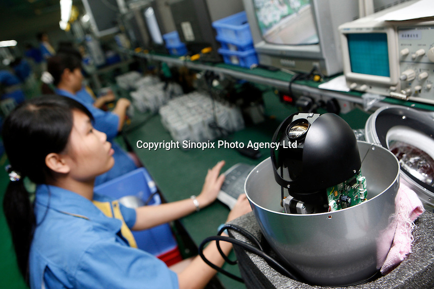 Workers assembling and testing security cameras at the China Security Surveillance and Technology factory in Shenzhen. At least 20,000 police surveillance cameras are being installed in Shenzhen operated with sophisticated computer software with face recognition technology..30 Aug 2007