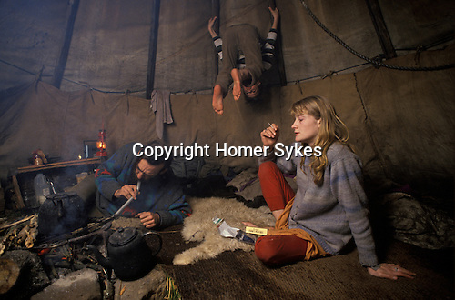 Llandeilo, Wales. 1980's    <br /> Brig Oubridge blows through a pipe to entice the campfire to glow a little brighter, while Irene smoking a roll-your-own contemplates life.  At hand is a box of The Original Cooks Matches - just in case.  Kevin, Brig's son hangs around and upside down from the tepee support poles.  Set in 70 acres, this eco friendly Welsh hippy community was home to around 120 free spirits.