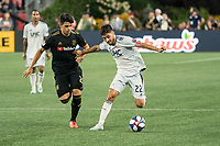 FOXBOROUGH, MA - AUGUST 4: Carles Gil #22 of New England Revolution under pressure from Adrien Perez #26 of Los Angeles FC during a game between Los Angeles FC and New England Revolution at Gillette Stadium on August 3, 2019 in Foxborough, Massachusetts.