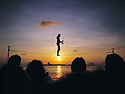 Man walking tight rope in Mallory square Key West, Florida at sunset. Crowd watching as man juggles.