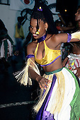 Salvador, Bahia State, Brazil. Girl in green, purple, white and yellow costume with grass decorations dancing at carnival.