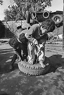 Children work as car mechanics in Pakistan - Child labor as seen around the world between 1979 and 1980 – Photographer Jean Pierre Laffont, touched by the suffering of child workers, chronicled their plight in 12 countries over the course of one year.  Laffont was awarded The World Press Award and Madeline Ross Award among many others for his work.