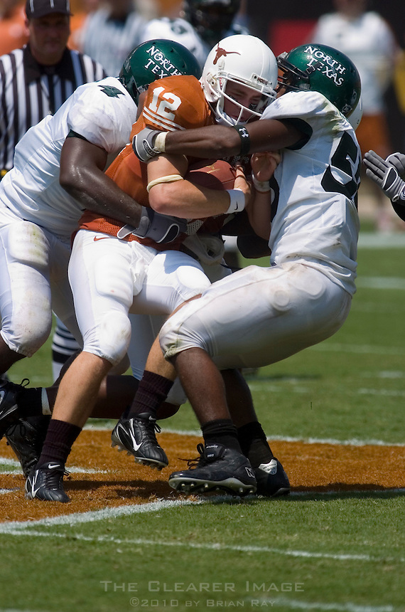 02 September 2006: University of Texas quarterback Colt McCoy is tackled by a host of University of North Texas defenders during the Longhorns 56-7 victory over the Eagles at Darrell K Royal Stadium in Austin, TX.