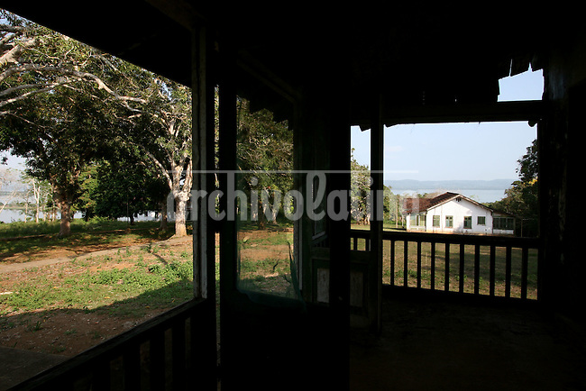 The executive housing area is seen through the porch of an abandonded home in Fordlandia, a former factory town created by the Ford Motor Company on the banks of the Tapajós River, September 6, 2005. Deep in the Amazon forest, 12 hours by boat from the regional capital of Santarem in Brazil's Pará state, the rubber plantation and processing factory is now abandoned to the rain-forest, an aging memorial to American ideals and to the Brazilian reality. It almost seems like time has stopped in Fordlandia, or better yet, time has passed it by. In typical american style, it was organized and efficient, an idea admired by many Brazilians, and perhaps more so by residents of the untamed Amazon. But It is an idea hard to implement in the wilds of the amazon. Some might also say that it is also a typical American style the way Ford came here and tried to implement something with little knowledge of the local customs or terrain. From 1928 to 1945, Ford came tried to take control of his rubber supply, one of the most important products of the rainforest. After only 17 years the company admitted defeat and retreated from the forest.