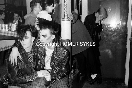 """Covent Garden, London. 1980 <br /> George O'Dowd, later know as Boy George, with friend Wilf Rogers at the Blitz Club, where George was working as the cloakroom attendant.  He is wearing a Malcolm McLaren cowboys t-shirt from Seditionaries based on a Jim French drawing.<br /> In reality George O'Dowd,had not assumed the name """"Boy George"""", at this time. He told me he was known as just George.<br /> Jim French (14 July 1932 - 16 June 2017) American photographer and illustrator.<br /> Princess Julia behind George O'Dowd, in profile."""
