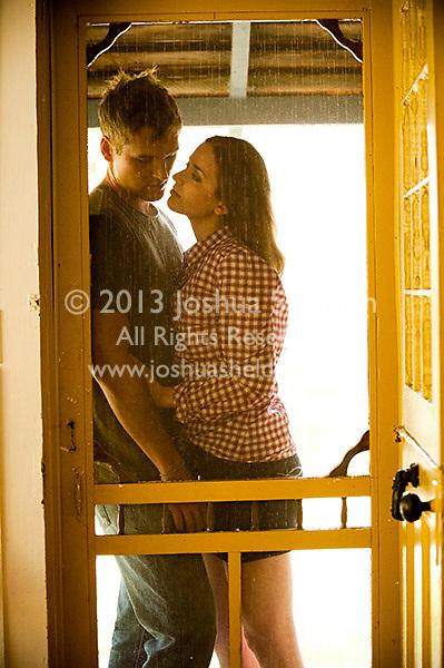 Young couple embracing against screen door
