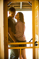 Young couple embracing against screen door