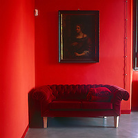 A portrait painting hangs above a red velvet sofa in the corner of a red room.