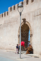 Essaouira, Morocco.  An Act of Charity: Giving Alms to a Beggar.