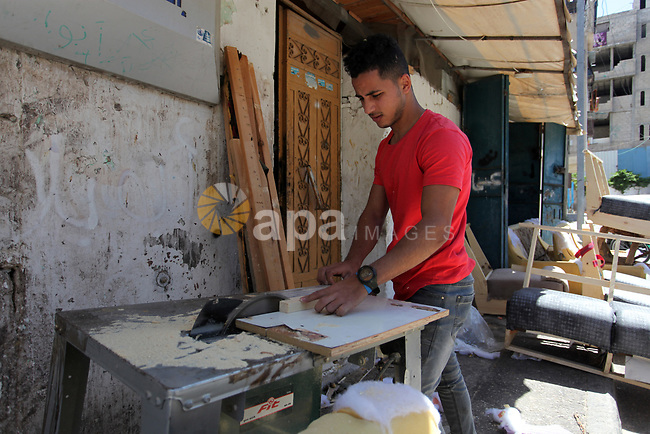 A Palestinian carpenter works at his workshop, marking International Workers' Day, in Gaza city, on May 01. 2021. Youth (19- 29 years) are the most group suffering from unemployment. Thus, the unemployment rate among youth reached about 39%; 24% in the West Bank and 67% in Gaza Strip. Moreover, the youth graduates of those who hold a scientific qualification of an intermediate diploma or higher are the most group suffering from unemployment, as this rate reached about 54%; (36% in the West Bank and 79% in Gaza Strip). Photo by Mahmoud Ajjour