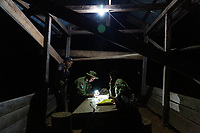 Military policemen and government environment rangers make records during an operation to confiscate illegally cut timber, during a night raid in rural northern Cambodia.
