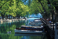 France, Annecy, Haute-Savoie, Rhone-Alpes, Europe, Wooden rowboats docked along the tree-lined Vasse canal on scenic Lake Annecy (Lac d' Annecy) in Annecy.