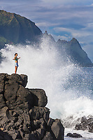 A woman standing on lava rocks opens her arms while waves break around her, Hanalei Bay, Kaua'i.