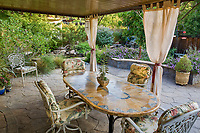 Table and chairs in backyard garden room with privacy curtains, outdoor stone patio, California drought tolerant garden