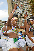 Dancers pass by the landmark Trellick Tower on Children's Day at Notting Hill Carnival