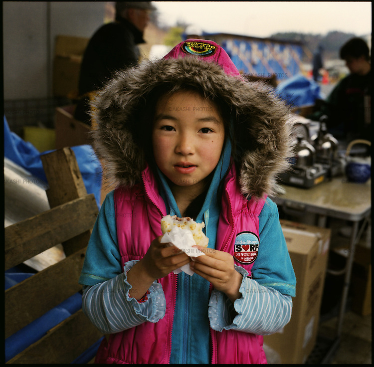 """Mika Suzuki, 10, eats Japanese sweets made by volunteers in a shelter in Minamisanriku, Miyagi, in one month after the earthquake and tsunami. The coast side of Minamisanriku was protected by the eight-meter-high water gate after the tsunami of 5 meters height in 1960 that killed 41 people. On March 11, 2011, the wave height of 15 meters (49 feet) went over the water gate and swallowed the whole town. The tsunami destroyed 70% of the 5600 houses in the town. Her house was also washed away. When the tsunami swallowed her town, she was in the school on the hill. The teachers called all students and counted the number of the students. The teachers decided not to move from the hill and stay over a night. Mika stayed up all night with other students and teachers. """"We had only three candles to spend a night,"""" she said. """"It was so cold and scary."""" The following day, his father walked through a mountain and reached the school to find Mika. """"I was so relived that my father showed up,"""" Mika said. They walked back together through a mountain and reunited with other members of family. <br /> On March 11, 2011, the earthquake of magnitude 9.0, the biggest earthquake in the history of Japan and the fourth biggest earthquake in the world after year 1900, shocked the Tohoku area of Japan. In about 30 minutes, devastating tsunami reached, affecting the coastline with a length of 500 km (310 miles). The tsunami wave height of 39 meters (128 feet) was recorded in a port town in Tohoku. The tsunami swallowed villages along the coast and washed away all houses. The earthquake and tsunami killed more than 15,800 people, and still more than 3,500 people are missing."""