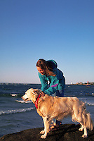 A woman on a beach with her Golden Retriever dog.