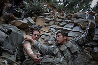 A US Army Medic treats Specialist Tenut from Viper Company 126, 2nd Platoon, who collapsed suffering from exhaustion during a mission in the restive Korengal Valley, epicentre of the war and scene of fierce fighting with the Taliban.