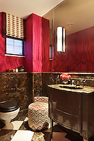 A lavishly decorated bathroom with dark marble wall cladding and a watered silk wallpaper