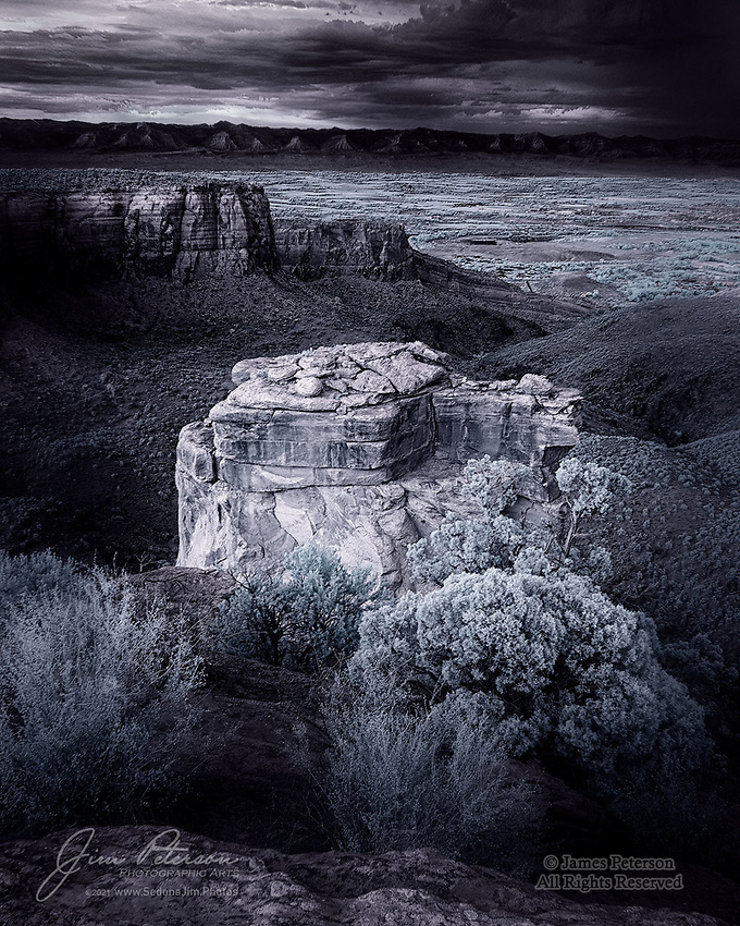 The View from Grand View (Infrared).  This is a twilight look across the Colorado River Valley from a view point along Rimrock Drive in Colorado National Monument.  Monsoon storms were gradually dissipating as the light faded, and the sandstone tower in the foreground took on a sublime infrared glow.  The towns of Fruita and Grand Junction can be seen in the distance.<br /> <br /> Tech info: Nikon D3200 camera with Nikon 18-140mm lens at 20mm, 1/30 sec. at f8, ISO 400.<br /> <br /> Image ©2021 James D. Peterson