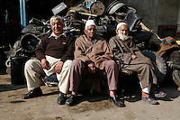 Three old men sit on of chairs in fron of a pile of old auto parts. Srinagar, Kashmir, India. © Fredrik Naumann/Felix Features