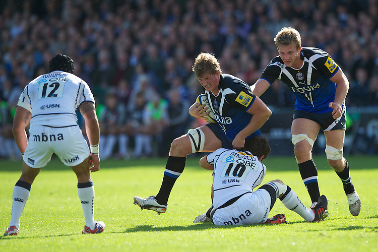 Stuart Hooper of Bath Rugby charges through the tackle of Nick MacLeod of Sale Sharks during the Aviva Premiership match between Bath Rugby and Sale Sharks at the Recreation Ground on Saturday 29th September 2012 (Photo by Rob Munro)
