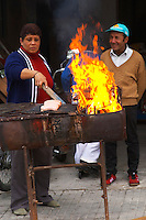 A market stall street market merchant selling lunch, barbecued sausages over an open fire barbecue in an old oil barrel, a man and a woman couple, the woman doing the grilling Montevideo, Uruguay, South America