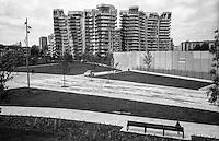 Milano, quartiere CityLife. Le Residenze Daniel Libeskind e una persona seduta ad una panchina --- Milan, CityLife district. The Libeskind Residences and a person sitting at a bench