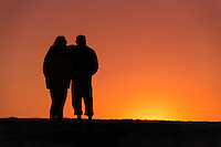 Senior couple enjoys the sunset from a jetty.