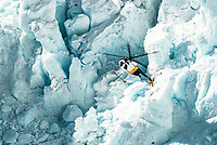 Helicopter flying among massive blocks of ice in Main Icefall on Franz Josef Glacier, Westland Tai Poutini National Park, West Coast, UNESCO World Heritage Area, New Zealand, NZ