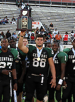 Miami Central Rockets defensive lineman Jordan Hinojosa #88 holds up the runner up trophy flanked by teammates Carnell Golden #27 and Donaldven Manning #1 after the Florida High School Athletic Association 6A Championship Game at Florida's Citrus Bowl on December 17, 2011 in Orlando, Florida.  Armwood defeated Miami Central 40-31.  (Mike Janes/Four Seam Images)