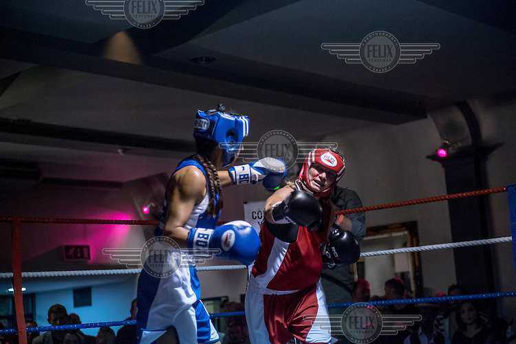 Emily Williams and Harvinder Jutte fight each other at a white collar boxing event at the London Irish Centre where the 'Carpe Diem' boxing event is taking place. <br /> <br /> 'White-collar boxing' is a growing phenomenon amongst well paid office workers and professionals and has seen particular growth in financial centres like London, Hong Kong and Shanghai. It started at a blue-collar gym in Brooklyn in 1988 with a bout between an attorney and an academic and has since spread all over the world. The sport is not regulated by any professional body in the United Kingdom and is therefore potentially dangerous, as was proven by the death of a 32-year-old white-collar boxer at an event in Nottingham in June 2014. The London Irish Centre, amongst other venues, hosts a regular bout called 'Carpe Diem'. At most bouts participants fight to win. Once boxers have completed a few bouts they can participate in 'title fights' where they compete for a replica 'belt'.