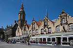 Belgium, West Vlaanderen, Veurne: Grote Markt with cyclists, restaurants and Saint Walburga`s Church tower (Saint Walburgakerk)
