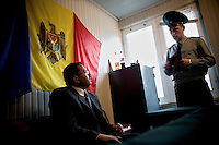 A border guard questions an Indian national who sits in front of  a Moldovan flag in a small customs post at a crossing point with Ukraine.