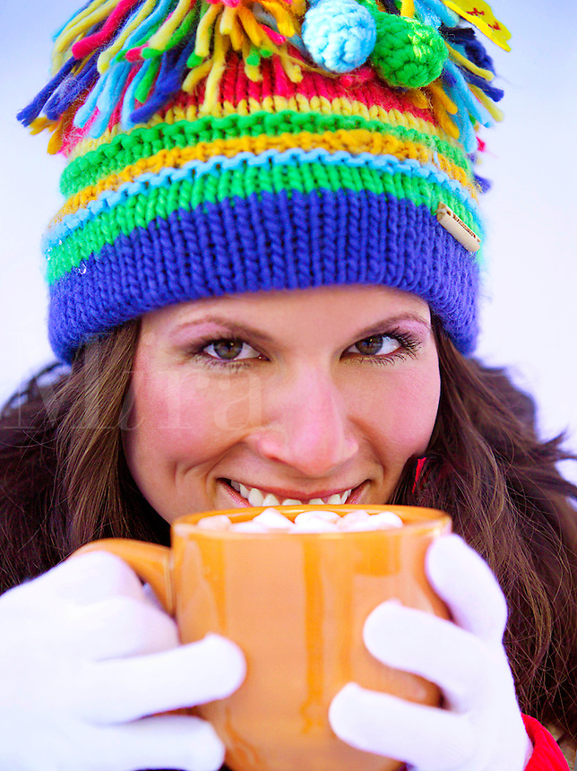 Woman in ski cap with mug of hot cocoa
