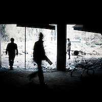 Refugees walk into a building where they squat.  Patras is home to about 3,000 illegal immigrants. Most of them are Afghans, although there are also some Iranians and Uzbeks. They stop in Patras to try and find passage to various European destinations by hiding in ships, containers and trucks parked in the port. If they are lucky they will make it to their destination. Many of them live in shacks made from cartons, plastic and wood they found on the beach. To shelter from the cold they also squat in abandoned buildings, living without water and electricity. The living conditions are inhumane and unhygienic.
