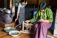 Bumthang, Bhutan.  Sitting on the Press Forces Buckwheat Flour through the Mold to Make Noodles.