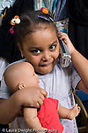 Education Preschool 3-4 year olds pretend play portrait of girl holding doll and telephone vertical looking at camera