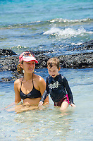 A local woman and girl play in tide pools at a beach in Puako, South Kohala, Island of Hawai'i.