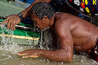 A Brazilian fisherman (jangadeiro) pushes the boat on the beach of Caponga, Ceará state, northeastern Brazil, 11 March 2004. Jangadeiros, working on a unique wooden raft boat called jangada, keep the tradition of artisan fishing for more than four hundred years. However, being a fisherman on jangada is highly dangerous job. Jangadeiros spend up to several days on high-sea, sailing tens of kilometres far from the coast, with no navigation on board. In the last two decades jangadeiros have been facing up the pressure from motorized vessels which use modern, effective (and environmentally destructive) fishing methods. Every time jangadeiros come back from the sea with less fish.