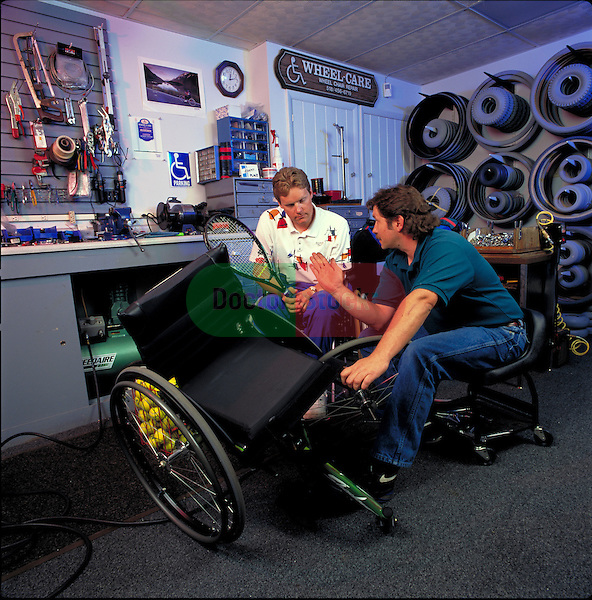 Technician services handicapped tennis player's sport's wheelchair