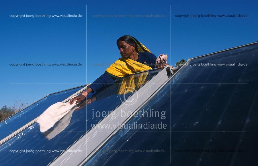 INDIA Rajasthan Mt. Abu , woman in yellow sari clean solar collector on rooftop at Brahma Kumari Ashram building / INDIEN Frau reinigt Solarkollektoren auf dem Dach eines Gebaeude des Brahma Kumari Ashram in Mount Abu