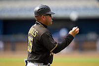 Coach Stephen Morales (35) throws in the first professional hit ball from FCL Pirates Black Henry Davis (not shown) during a game against the FCL Rays on August 3, 2021 at Charlotte Sports Park in Port Charlotte, Florida.  Davis was making his professional debut after being selected first overall in the MLB Draft out of Louisville by the Pittsburgh Pirates.  (Mike Janes/Four Seam Images)