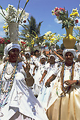 Itaparica Island, Bahia, Brazil. Baiana women carrying flowers on their heads for Iemanja celebration.