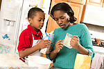 Mother and son, age 5, in kitchen, baking, measuring and pouring ingredients, mother showing child how far up to fill measuring cup