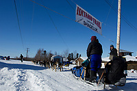 Karin Hendrickson passes under the checkpoint banner at the Shageluk village checkpoint during the 2011 Iditarod race.